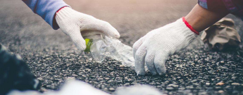 Hands wearing gloves picking up a plastic bottle