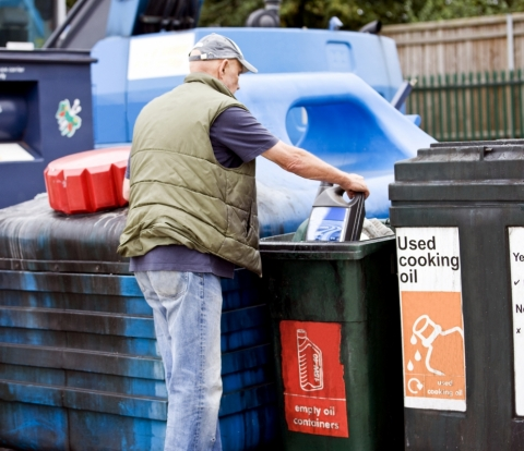 A older gentleman putting an oil container in a recycle bin