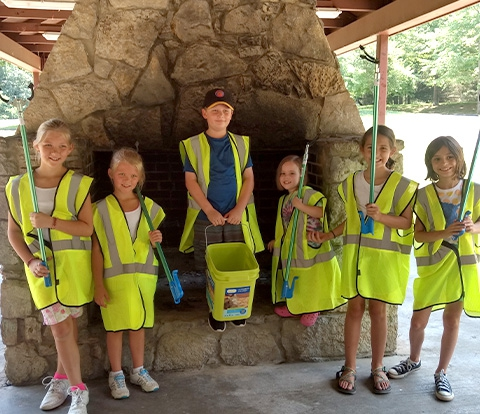 Group of kids holding tools to clean up litter